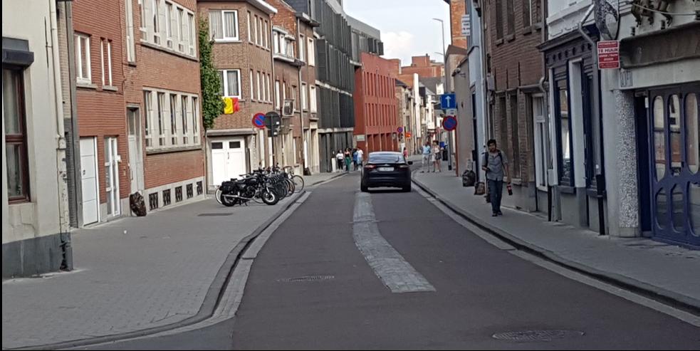 asfalterad gata med bred mittremsa av gatsten