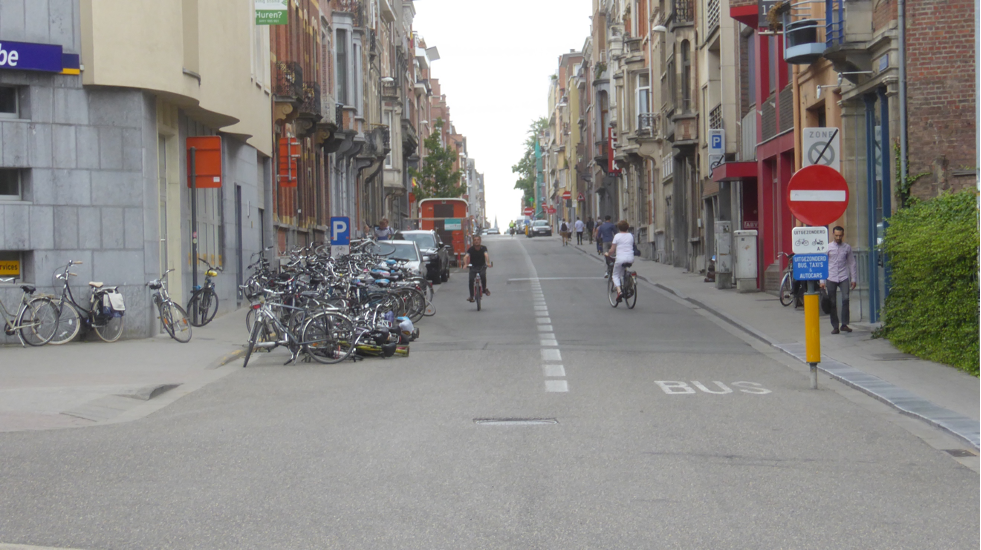Gata med parkerade cyklar och bilar och två cyklister som möts